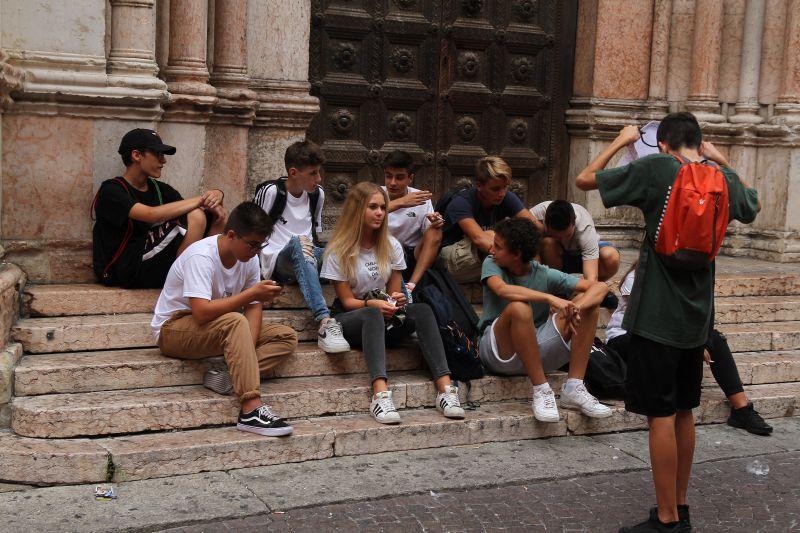 Foto Luigi Boschi: ragazzi seduti e riuniti sui gradoni del Battistero di Parma